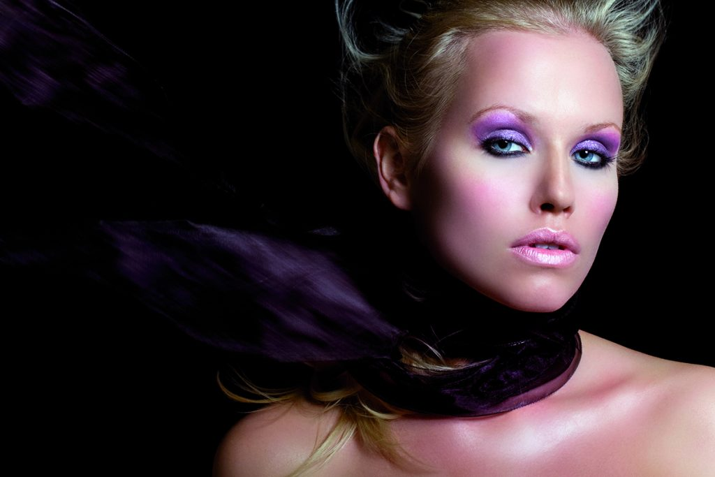 Model with makeup in purple tones.